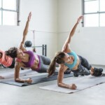 female-athletes-doing-side-plank-pose-in-gym-royalty-free-image-961013784-1567189051